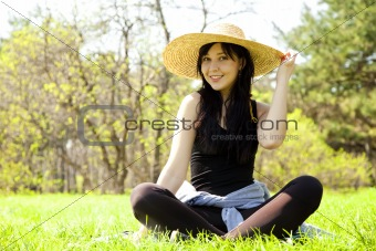 Beautiful brunette girl in hat at the park.