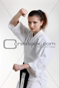 Karate. Young girl in a kimono with a white background