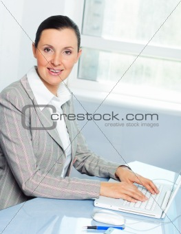 Attractive smiling young business woman using laptop