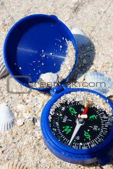 Dark blue compass on sand