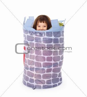 Little girl hides in toy basket