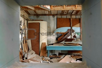ramshackled room with boarded up window