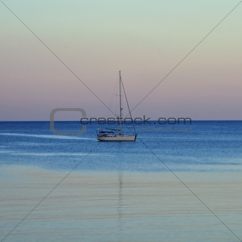 sailboat reflected on sea water