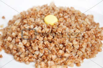 Appetizing crumbly buckwheat with butter on white background