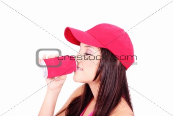 Cute brunette sipping of a can wearing a red hat
