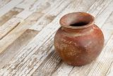 red clay pot on rustic table