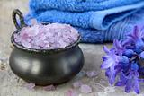 Spa still life .Bath lilac salt, towel and  flowers