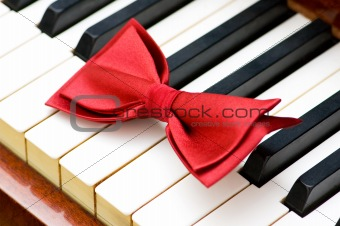 Red bow tie on the piano keys