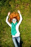 Girl lies at green grass in the park.