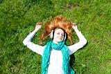 Redhead girl with headphone lies in the park.