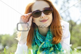 Beautiful red-haired girl in sunglasses at the park.