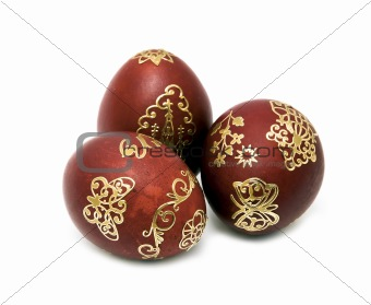 three nice gold decorated Easter eggs closeup over white
