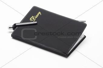 Black pocket diary and ballpoint pen