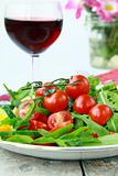 salad with arugula and cherry tomatoes with a glass of wine in the background