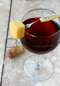 A glass of red wine with a slice of cheese for a snack