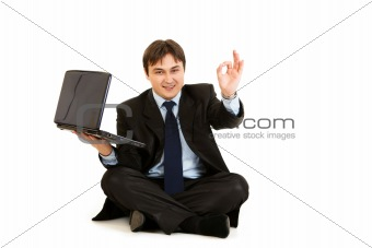 Sitting on  floor with laptop smiling businessman showing ok gesture