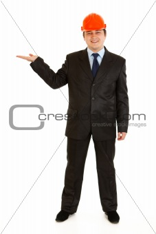Smiling businessman in helmet  on head presenting something on empty hand