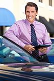Businessman Leaning on Car with Tablet Computer