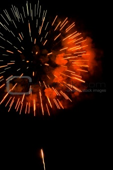 A burst of orange-red fireworks against a night sky.