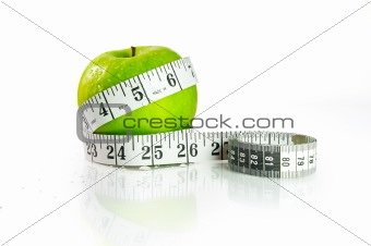 A green apple with measuring tape