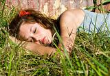 Beautiful teenage girl sleeping in a field