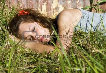 Beautiful teenage girl sleeping in a field