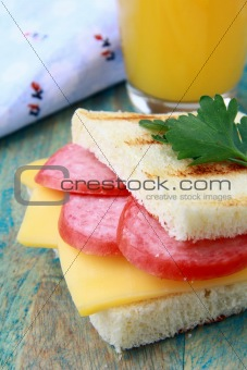 breakfast sandwich with cheese and salami and juice
