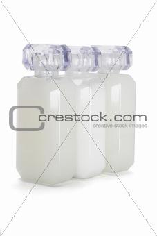 Three glass bottles of toiletries