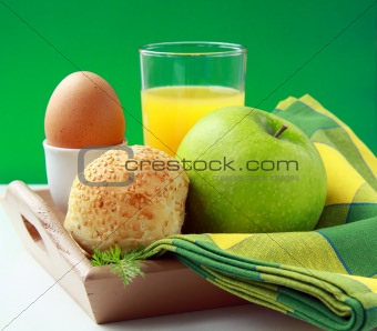 breakfast with orange juice, boiled egg and sesame buns and  green apple