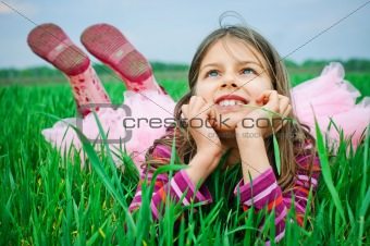A beautiful little girl lying in the grass