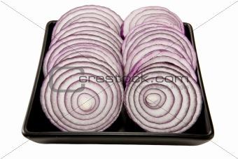 Sliced onions on a black plate