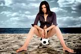 model on a football at the beach