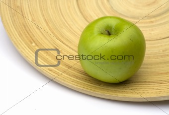 Green apple on a bamboo plate