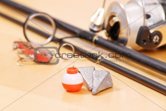 Fishing Weights and Floater Next to Black Fishing Rod