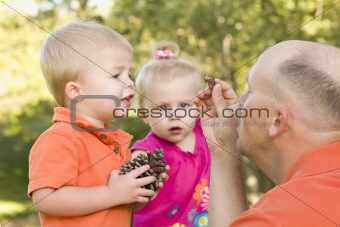 Cute Twin Children Talk with Dad about Pine Cones in The Park.