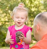 Adorable Young Girl Holding Pine Cone Talks to Her Dad in The Park.