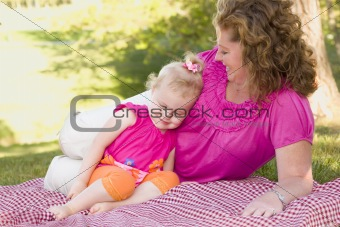 Loving Moment with Attractive Mother and Adorable Daughter on Picnic Blanket in the Park.