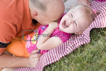 Loving Dad Tickles His Daughter in the Park.