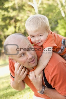 Father and Son Piggyback Ride in the Park.