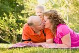 Affectionate Couple Kiss as Adorable Son Watches in the Park.