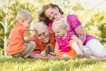 Young Caucasian Family Enjoying Pinecones at The Park Together.