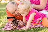 Handsome Father and Adorable Young Daughter Talk about Pine Cone in the Park.
