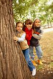 Friends behind tree