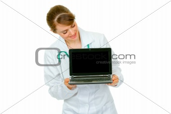 Smiling  medical doctor woman looking on laptop with blank screen