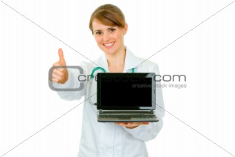 Smiling  medical doctor woman holding laptop with blank screen and showing thumbs up gesture