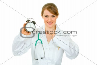 Smiling  medical female doctor pointing finger on alarm clock