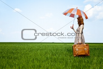 Redhead enchantress with umbrella and suitcase