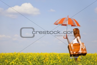 Redhead enchantress with umbrella and suitcase at spring rapeseed