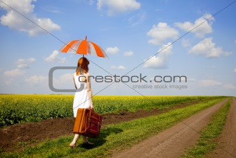 Redhead enchantress walking near rapeseed field.