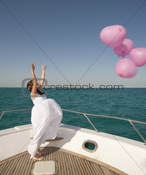 Bride releasing balloons from a boat